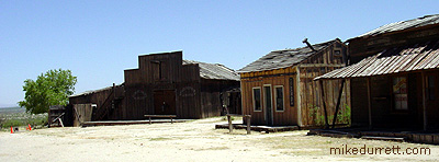 The livery stable at the Mescal movie location hides the parking lot from cameras. Looks authentic down to the orange Old West traffic cones. Photo copyright 2003-2004 Mike Durrett, all rights reserved.